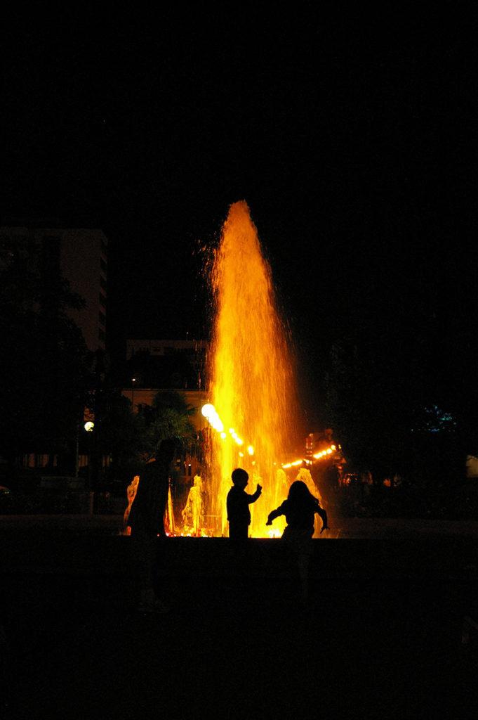 """""""10 years challenge"""" : mon évolution photographique. Photo de nuit en contre-jour avec des enfants qui jouent devant une fontaine illuminée."""
