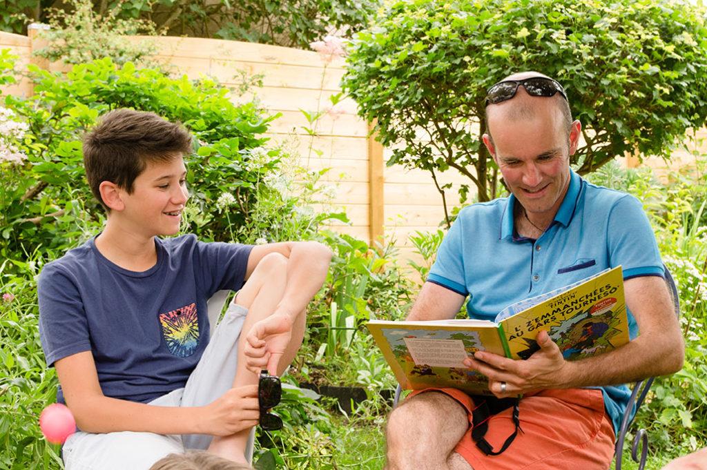 Comment vivre sa vie de famille au présent ? Photographie d'un père et son fils qui partagent un moment ensemble dans la bonne humeur.