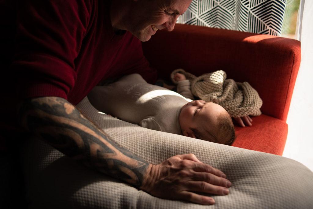 Reportage du quotidien près de Rennes. Photographie couleur d'un papa communiquant avec son bébé.