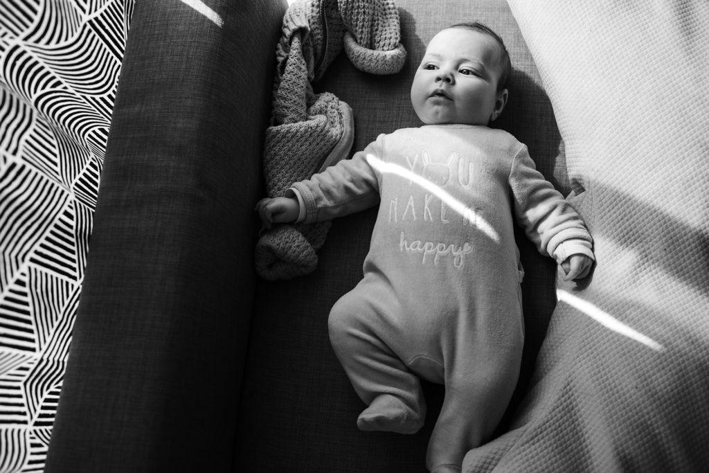 Reportage du quotidien près de Rennes. Photographie en noir et blanc d'un bébé allongé sur un canapé.