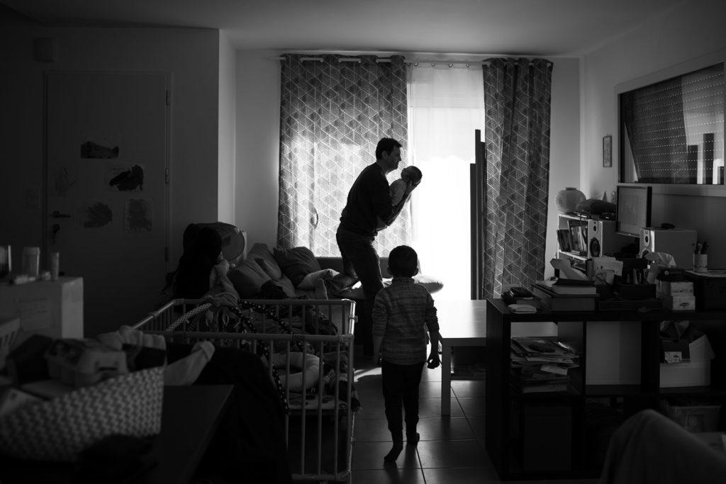 Reportage du quotidien près de Rennes. Photographie en noir et blanc d'un papa portant son bébé en contre-jour.
