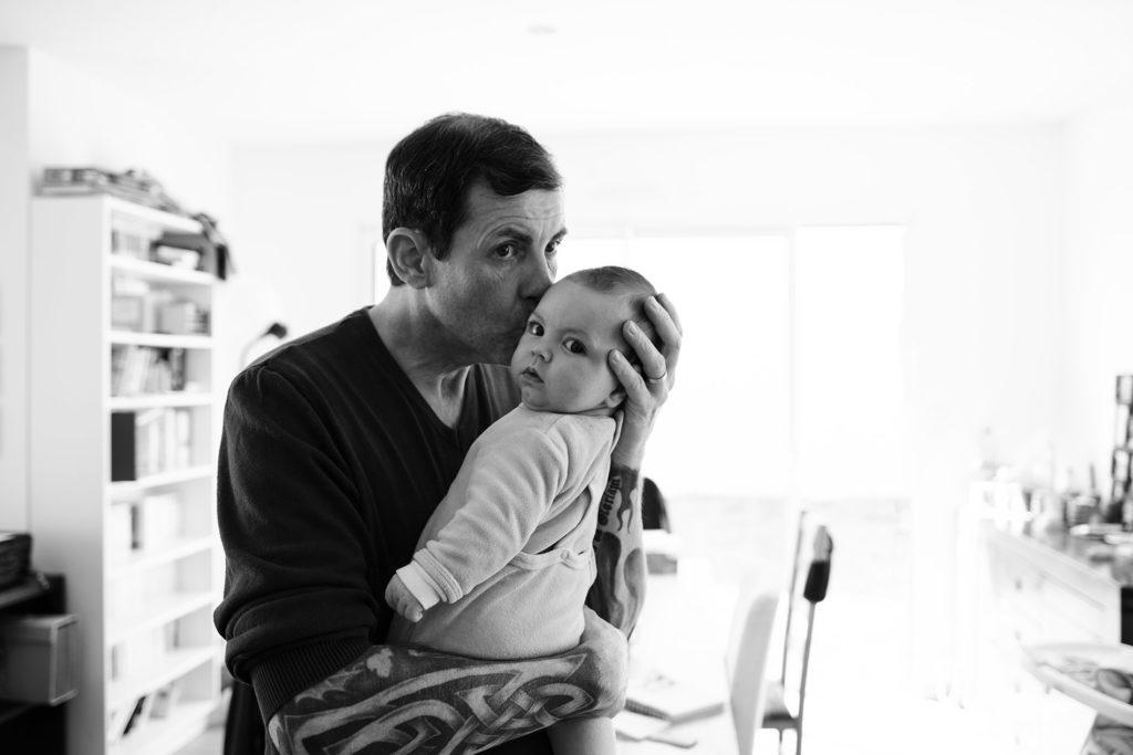 Reportage du quotidien près de Rennes. Photographie d'un papa embrassant son bébé.