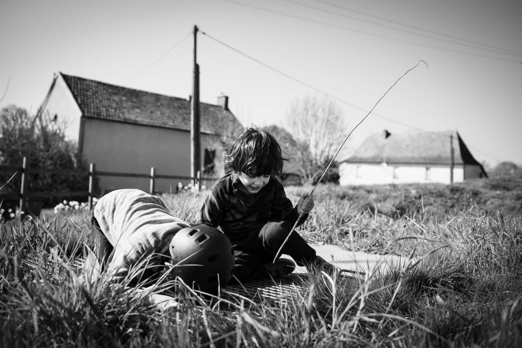 Reportage du quotidien près de Rennes. Photographie noir et blanc d'enfants jouant dehors.