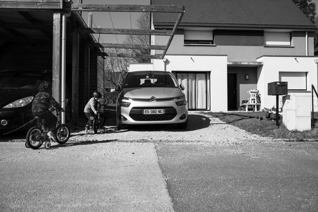 Reportage du quotidien près de Rennes. Photographie en noir et blanc d'enfants jouant devant une maison.