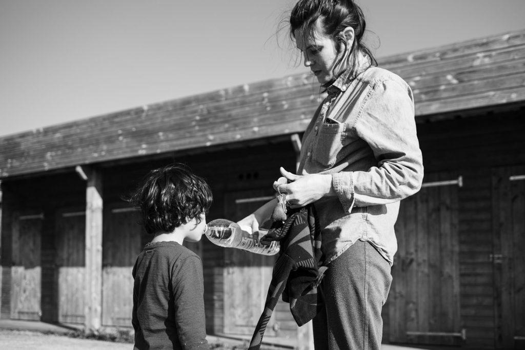 Reportage du quotidien près de Rennes. Photographie en noir et blanc d'une maman donnant à boire à son fils en extérieur.