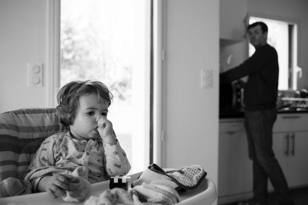 Reportage du quotidien près de Rennes. Photographie en noir et blanc d'un enfant à peine réveillé et de son papa préparant son gouter.