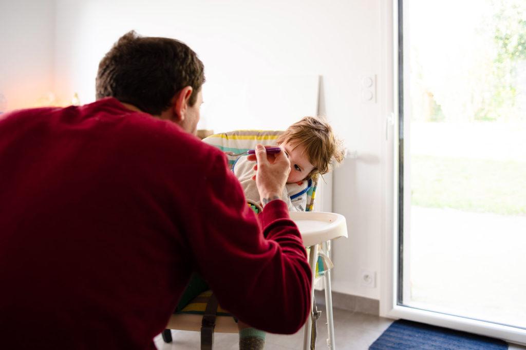 Reportage du quotidien près de Rennes. Photographie représentant un papa donnant le gouter à son fils.