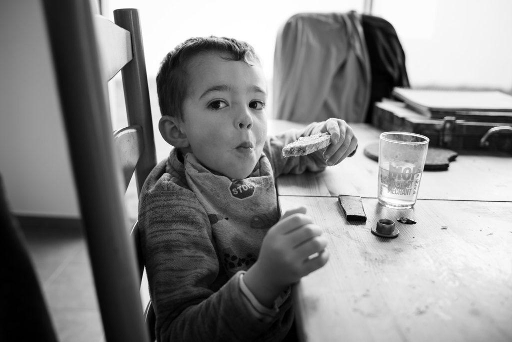 Reportage du quotidien près de Rennes. Photographie en noir et blanc d'un petit garçon prenant son gouter.
