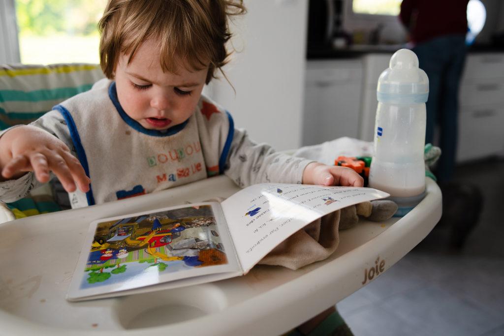 Reportage du quotidien près de Rennes. Photographie d'un jeune enfant dans sa chaise haute lisant un livre.
