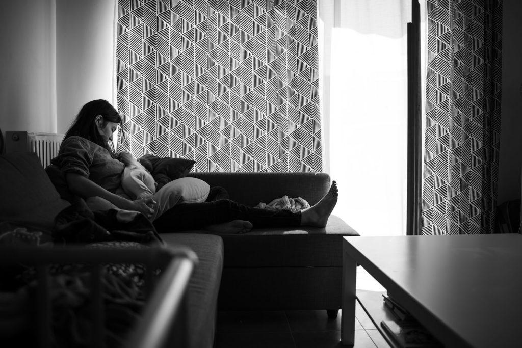 Reportage du quotidien près de Rennes. Photographie noir et blanc d'une maman allaitant son enfant.