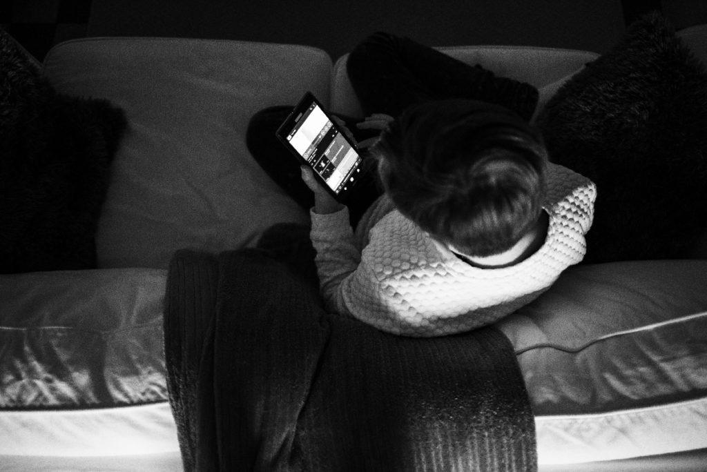 Le rapport des ados à la photographie.  Photographie en noir et blanc d'une ado qui regarde son téléphone.