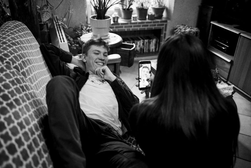 Le rapport des ados à la photographie. Photographie en noir et blanc d'une jeune fille qui photographie un autre ado avec son téléphone.