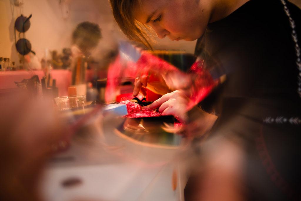 Comment rester créatif en photographie de portrait ? Photographie d'une jeune fille qui réalise une activité manuelle.