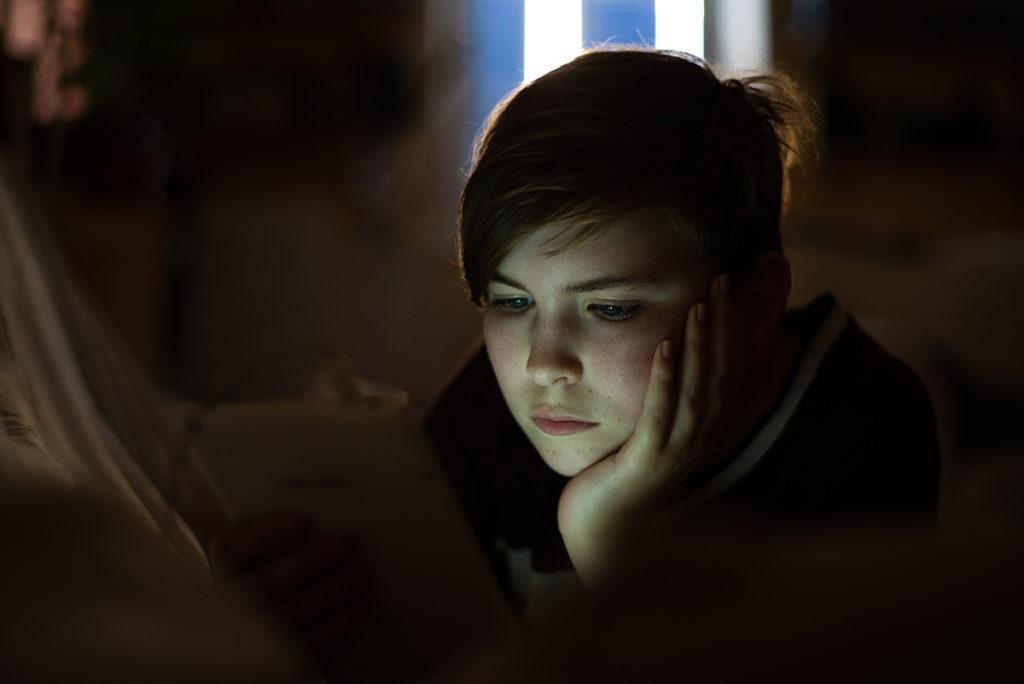 Portraits en faible lumière. Jeune fille en contre-jour éclairer par la lumière de sa tablette.