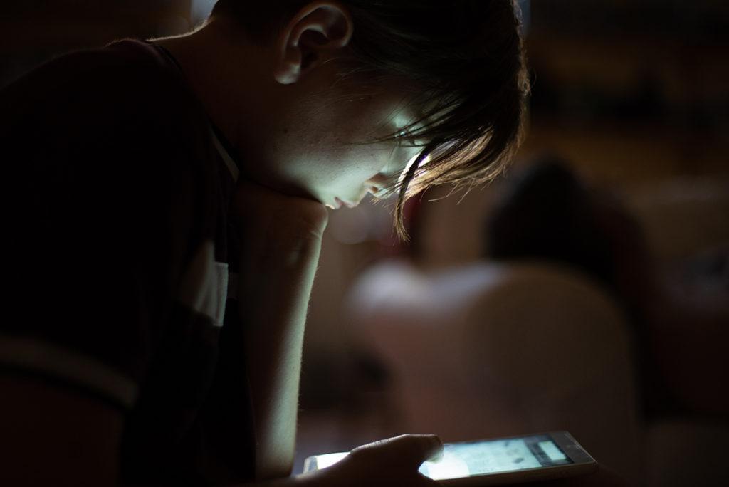 Portraits en faible lumière. Jeune fille regardant sa tablette.