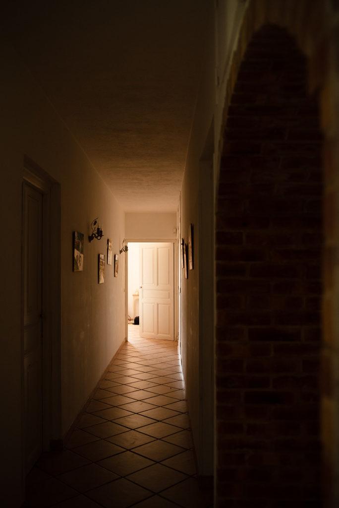 Porte ouverte au fond d'un couloir.