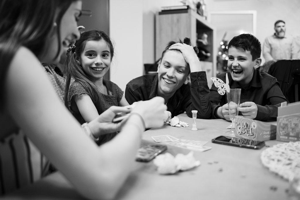 Comment vivre sa vie de famille au présent ? Photographie en noir et blanc d'adolescent partageant un jeu dans une ambiance joyeuse.