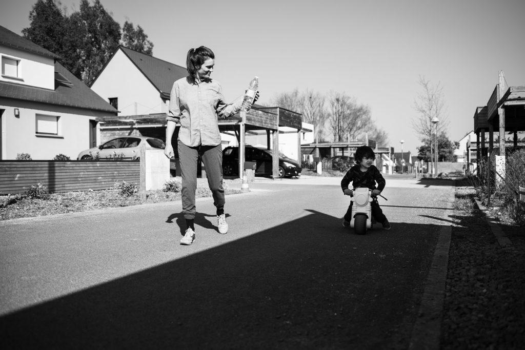 Reportage du quotidien près de Rennes. Photographie en noir et blanc d'une maman et de son fils en vélo à l'extérieur.