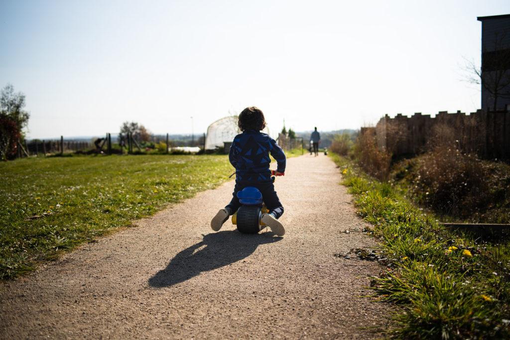 Reportage du quotidien près de Rennes. photographie représentant un enfant de dos en contre-jour sur son vélo.