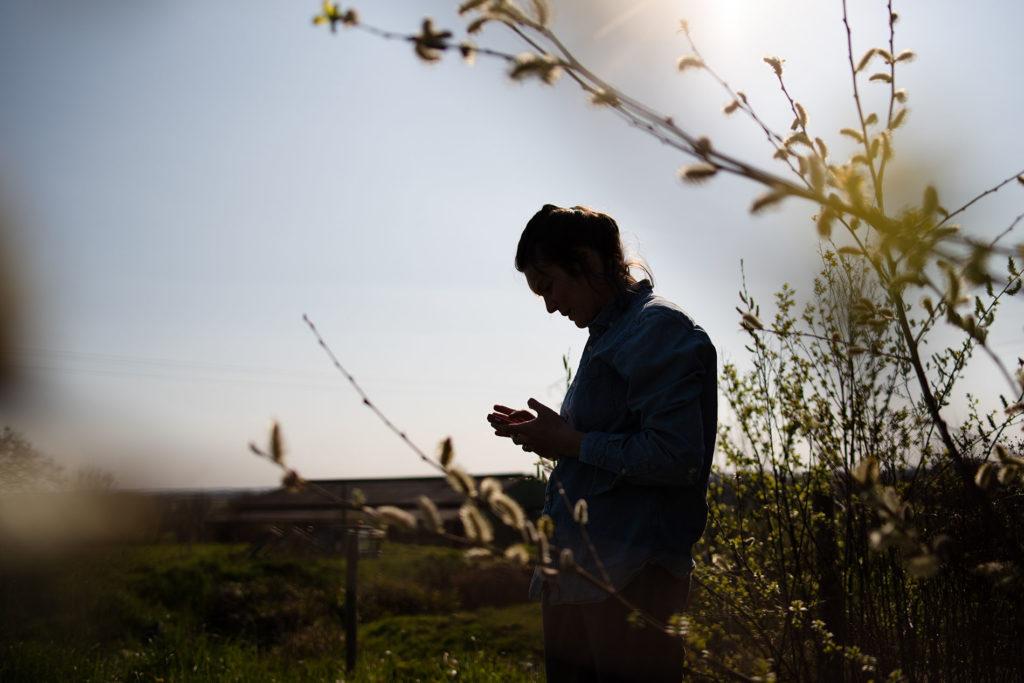 Reportage du quotidien près de Rennes. Portrait en contre-jour d'une femme regardant son téléphone dans la nature.
