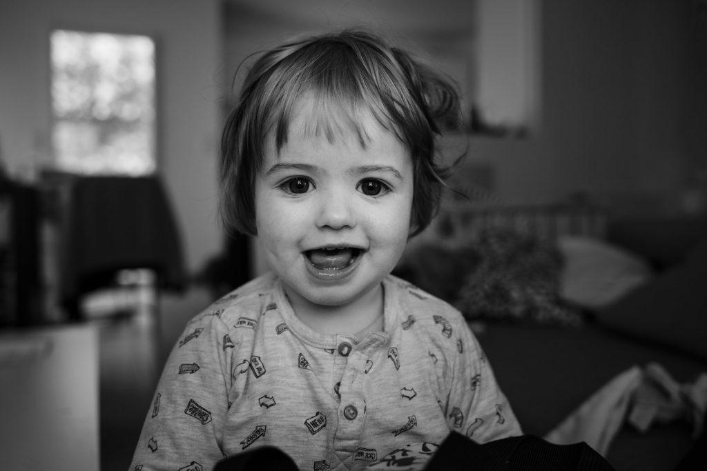 Reportage du quotidien près de Rennes. Portait en noir et blanc d'un jeune enfant souriant.