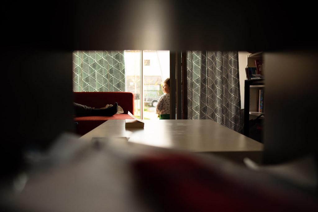 Reportage du quotidien près de Rennes. Photographie d'un jeune enfant devant une baie vitrée avec une belle lumière.