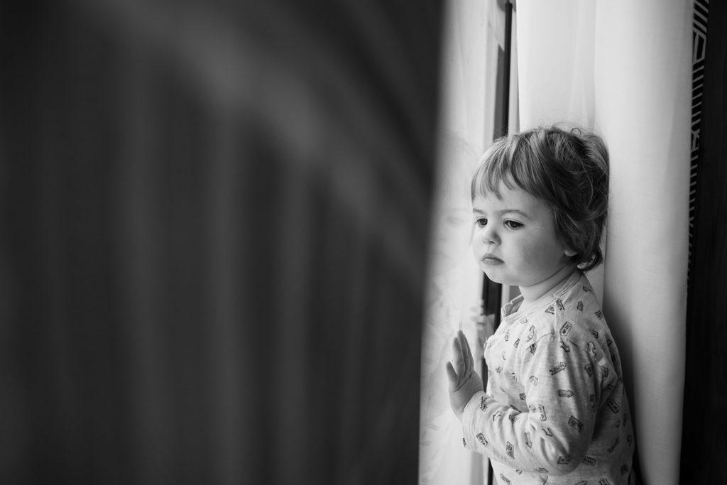 Reportage du quotidien près de Rennes. Portrait noir et blanc d'un jeune enfant regardant par une baie vitrée d'un air rêveur.