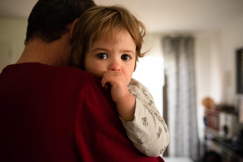 Reportage du quotidien près de Rennes. Portrait d'un jeune enfant qui vient de pleurer dans les bras de son papa.