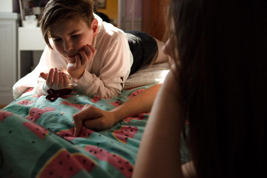 Le rapport des ados à la photographie.  Photographie en couleur de deux adolescentes sur un lit.