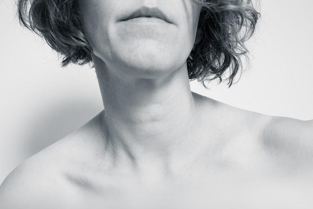 Pourquoi réaliser des autoportraits ? Photographie en noir et blanc. Epaules nues, visage coupé.