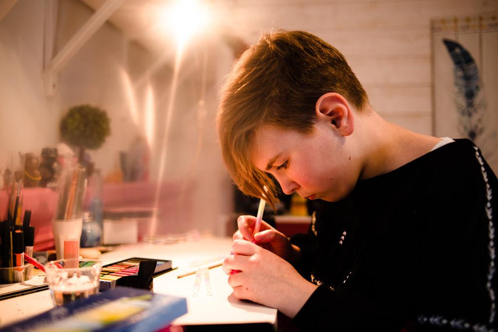 Comment rester créatif en photographie de portrait ? Portrait d'une jeune fille qui réalise une activité manuelle.