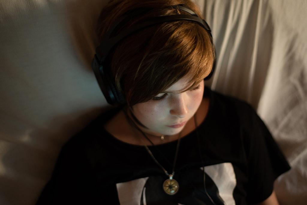 Portraits en faible lumière. Photographie d'une jeune fille sur un canapé, lumière chaude de fin de journée.