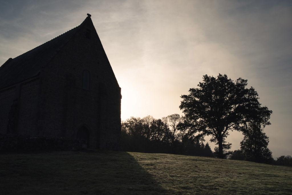 Sortie nature à la chapelle du Montaigu, en Mayenne. Vue imposante de la Chapelle du Montaigu en contre-jour sous la lumière matinale.