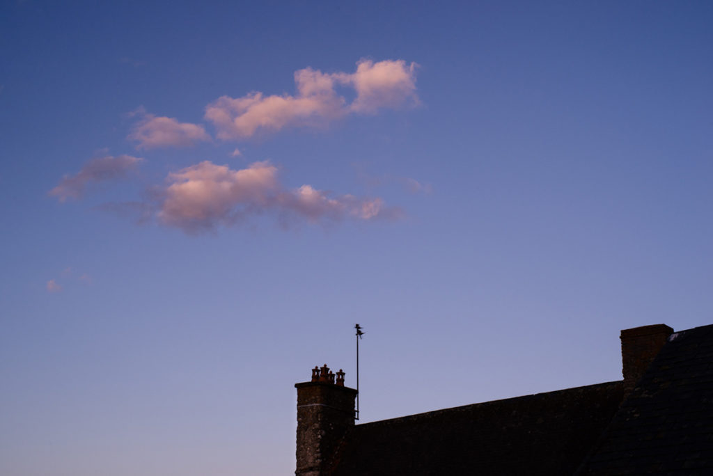 Cours de photographie débutant. Photographie à l'heure bleue : nuage rosé au dessus d'un toit.