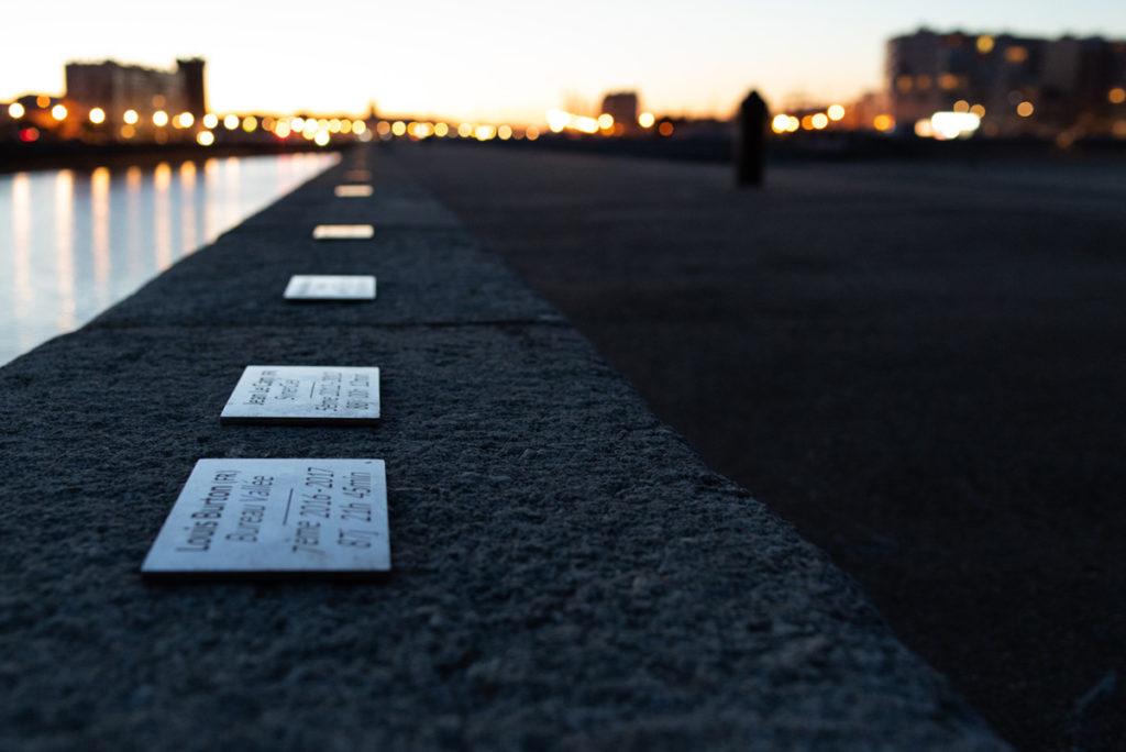 Cours de photographie débutant. Photographie à la nuit tombée du chenal des Sables d'Olonne au ras des plaques des participants du Vendée Globe.