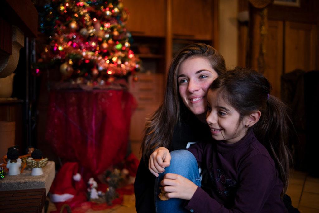 Offre reportage découverte. Photographie de famille à Noël lors d'un reportage. Portrait de deux jeunes filles. Photographe Pascaline Michon.