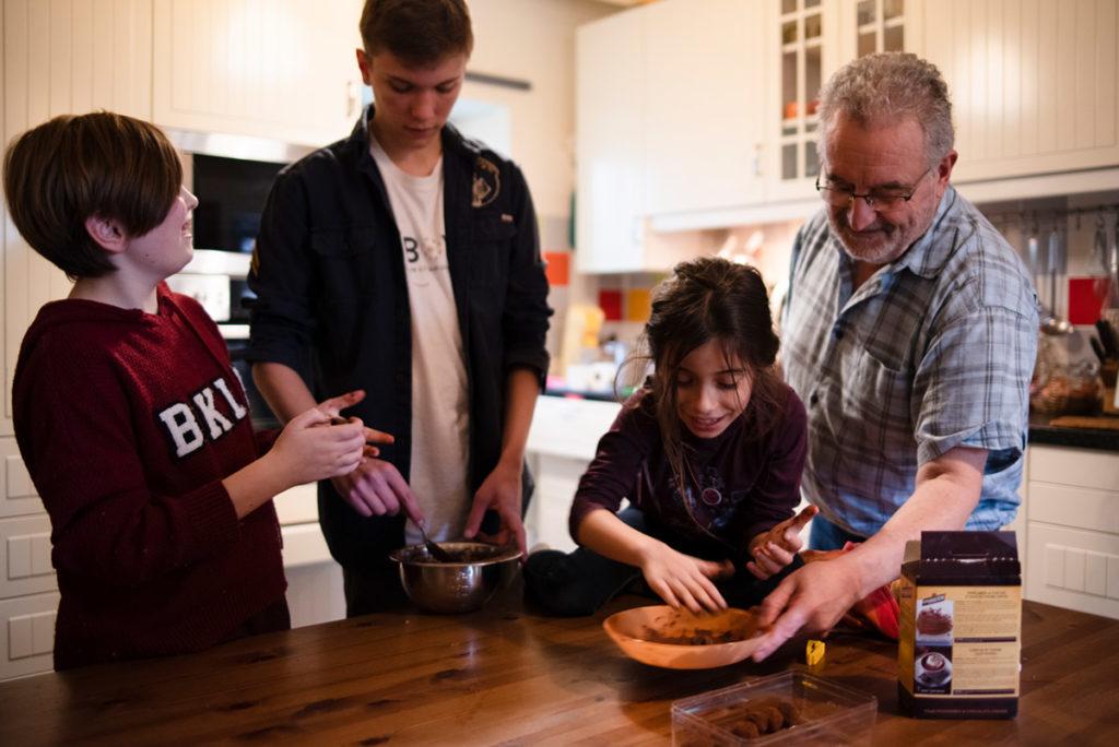 Offre reportage découverte. Photographie d'un reportage de famille autour de Noël. Des enfants préparent des truffes au chocolat avec leur grand-père. Photographe Pascaline Michon.