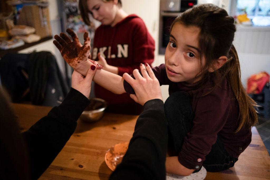 Offre reportage découverte. Photographie d'un reportage de famille autour de Noël. Des enfants préparent des truffes au chocolat. Photographe Pascaline Michon.