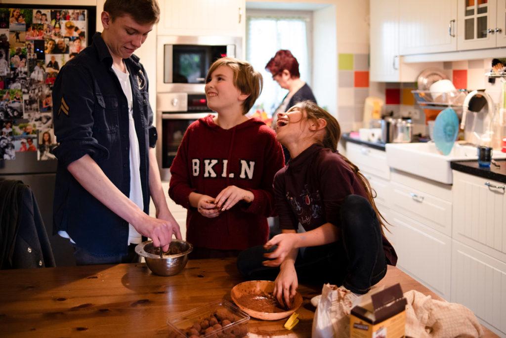 Offre reportage découverte. Photographie d'un reportage de famille autour de Noël. Des enfants préparent des truffes au chocolat dans la bonne humeur. Photographe Pascaline Michon.