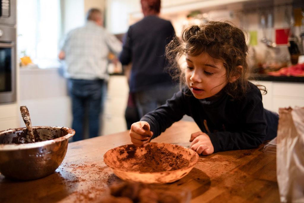 Offre reportage découverte. Photographie d'un reportage de famille autour de Noël. Des enfants préparent des truffes au chocolat. Portrait d'une petite fille mettant les doigts dans le chocolat en poudre. Photographe Pascaline Michon