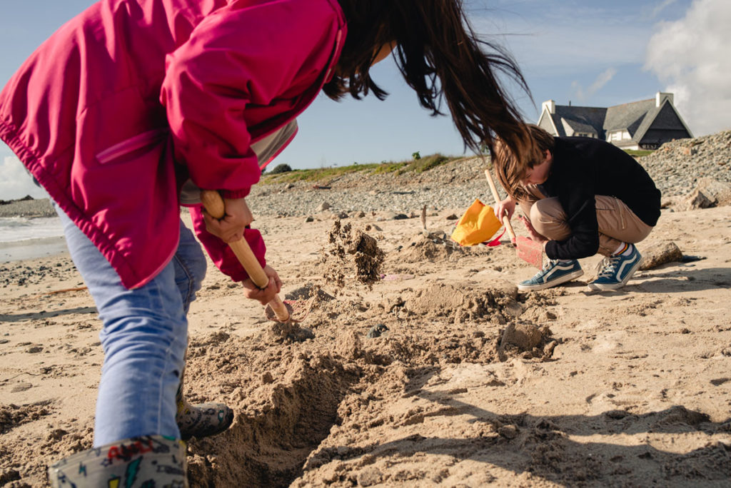 Reportage de famille à Plozevet. Photographie d'enfants jouant sur la plage à l'occasion d'une séance de famille.