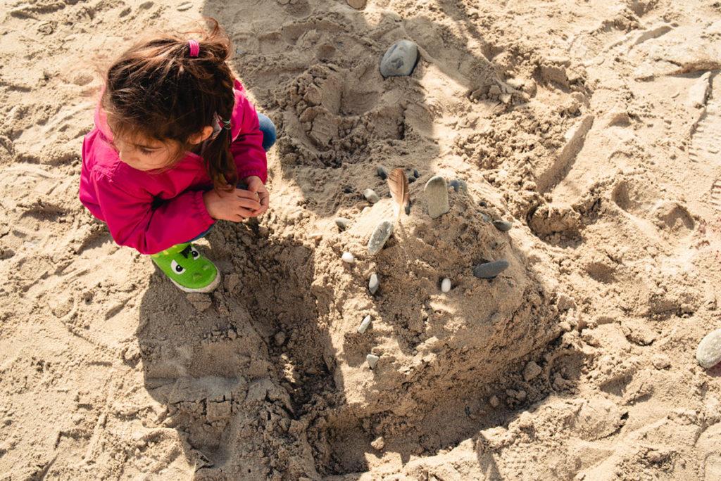 Reportage de famille à Plozevet. Vue plongeante d'une enfant construisant un château de sable. Séance de famille.