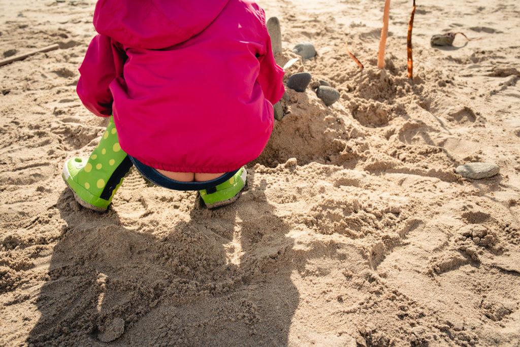 Reportage de famille à Plozevet. Photographie humoristique d'une enfant sur la plage.