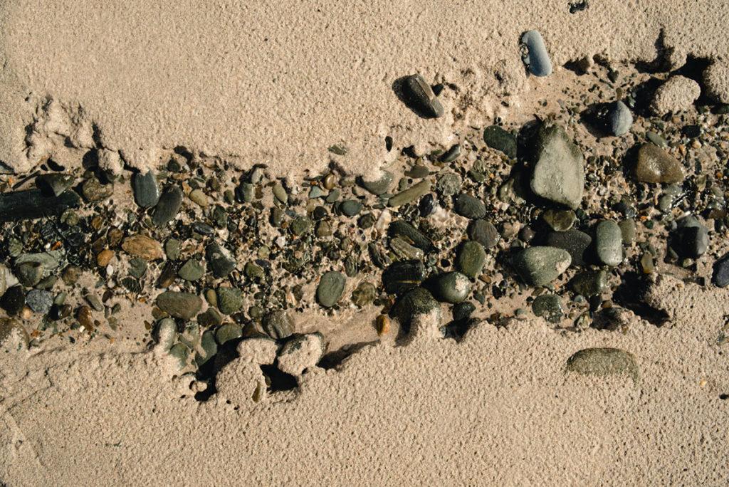 Reportage de famille à Plozevet. Photographie de galets sur la plage dans un filet d'eau.