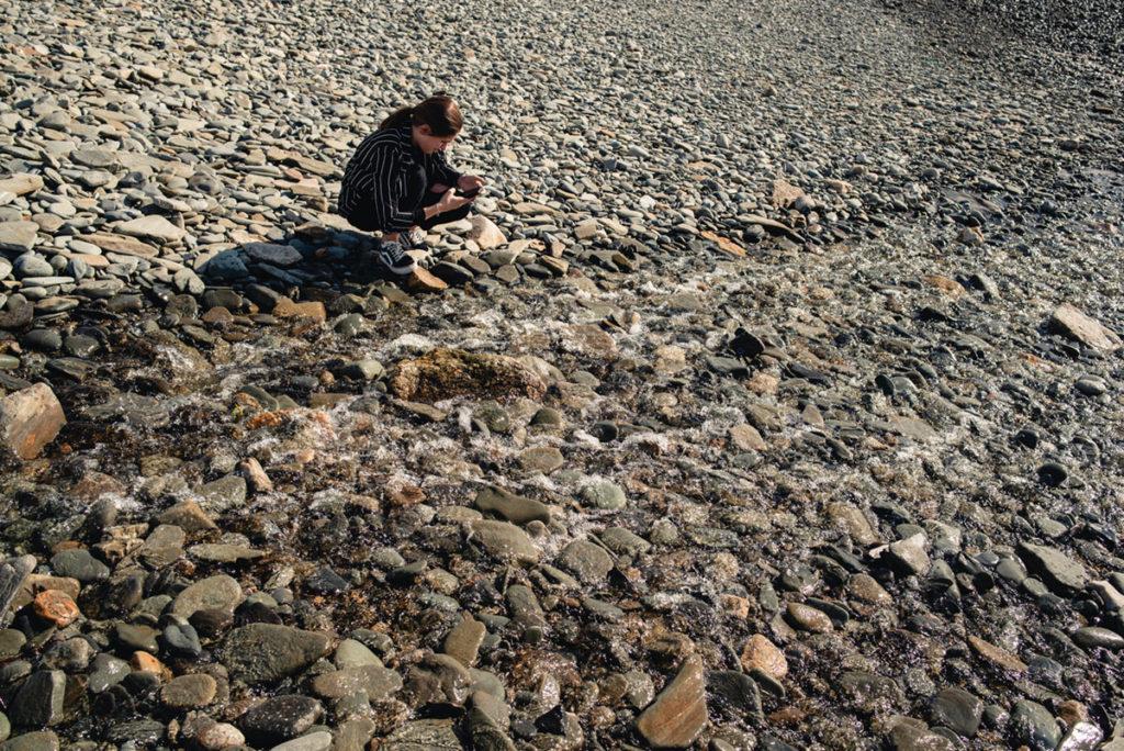 Reportage de famille à Plozevet. Une adolescente photographie avec son téléphone les galets sur la plage. Séance famille.