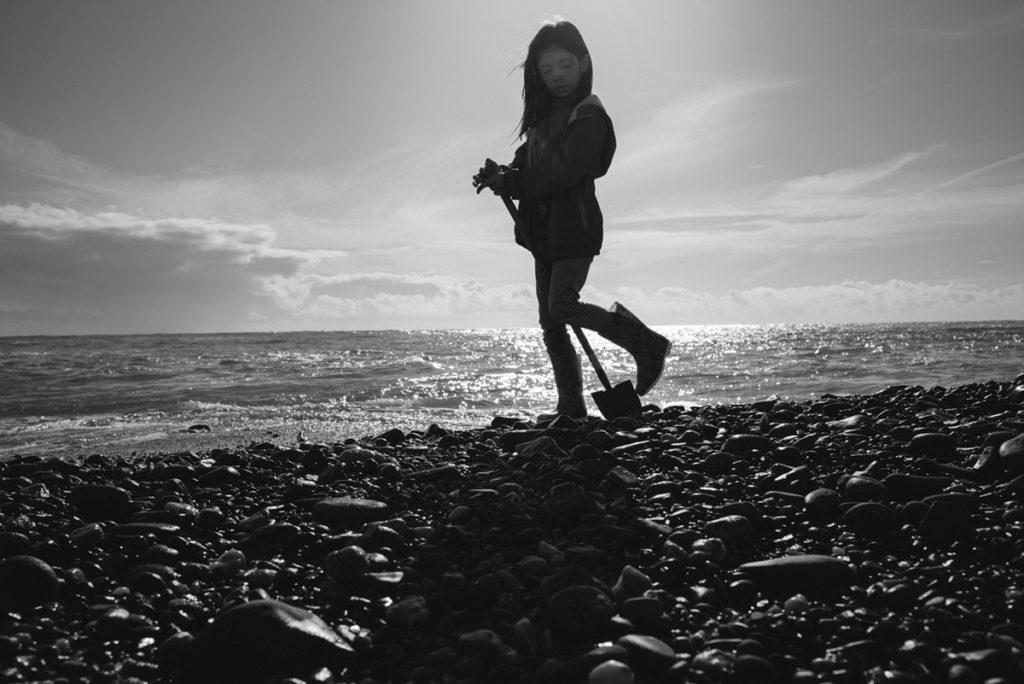 Reportage de famille à Plozevet. Photographie en noir et blanc d'une enfant recherchant des coquillages sur la plage. Séance reportage de famille.