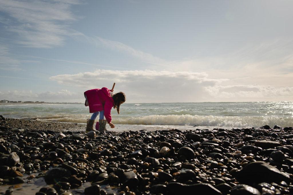 Reportage de famille à Plozevet. Enfant recherchant des coquillages sur la plage. Séance reportage de famille.