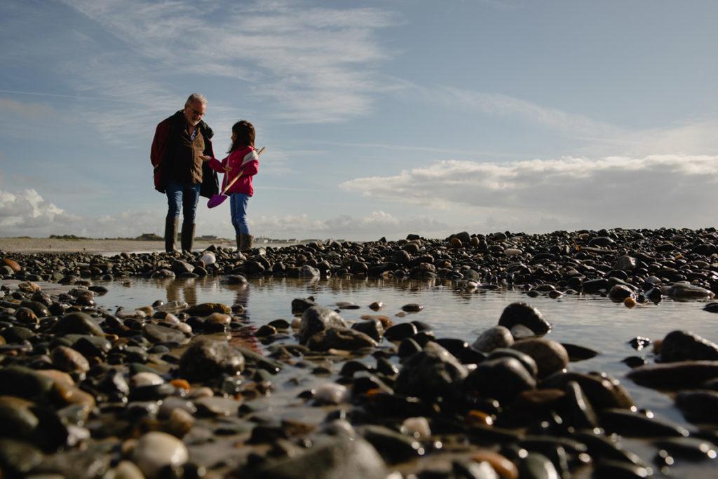 Reportage de famille à Plozevet.  Enfant montrant à son grand-père coquillage trouvé sur la plage. Séance reportage de famille.