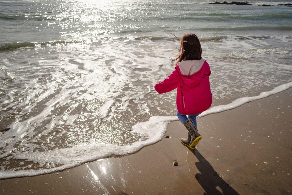 Reportage de famille à Plozevet. Enfant jouant avec les vagues lors d'un reportage de famille.