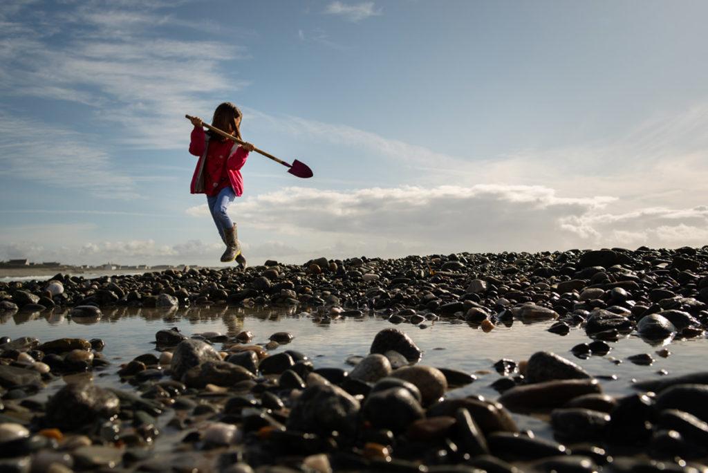 Reportage de famille à Plozevet. Une enfant joue sur la plage. Séance reportage de famille.